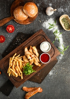 Pollo frito y papas fritas en una tabla de madera