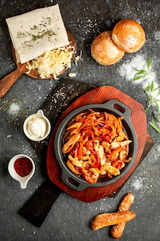 Pollo frito con pimiento y cebolla en una sartén de aluminio