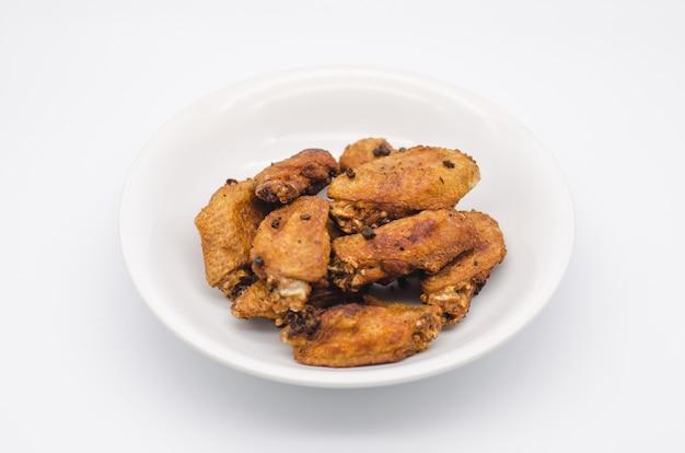 Pollo frito en un plato blanco con fondo blanco, comida asiática, comida poco saludable
