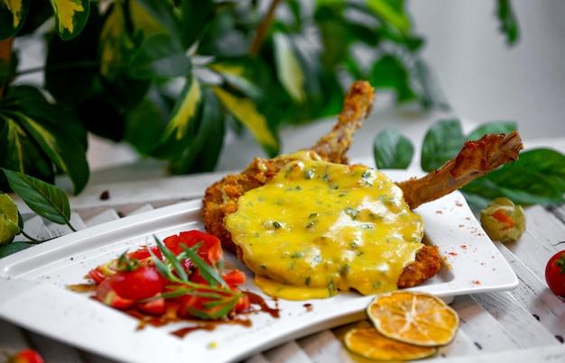 Pollo frito bajo salsa de queso en el plato