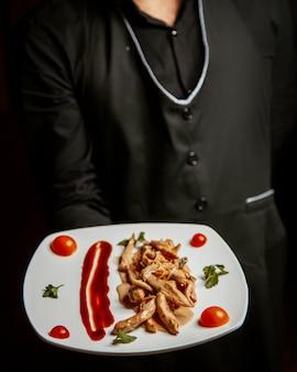Pollo frito bajo salsa sobre la mesa