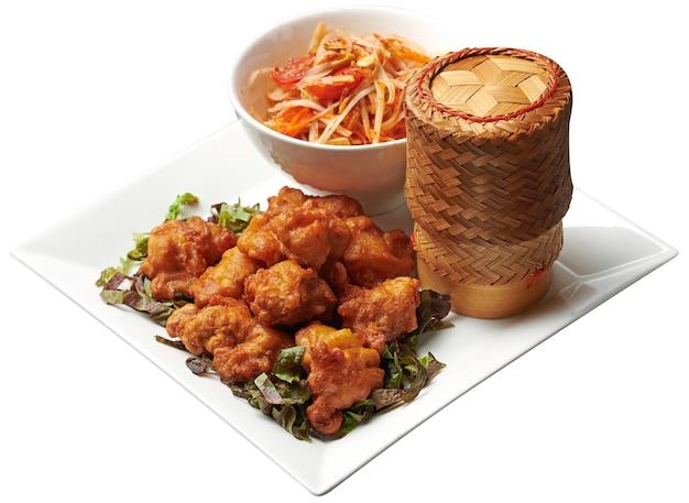 Pollo frito servido con ensalada de papaya y arroz pegajoso