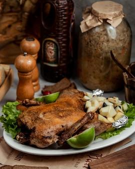Pollo frito con verduras y frutas en la mesa