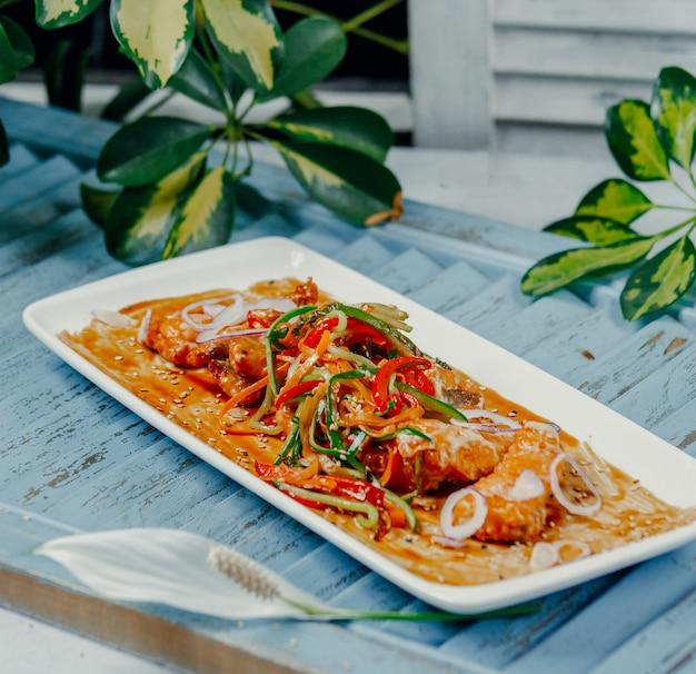 Pollo frito con verduras en la mesa