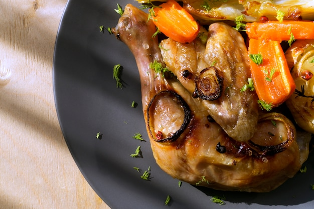 Pollo frito con verduras. en un plato gris.