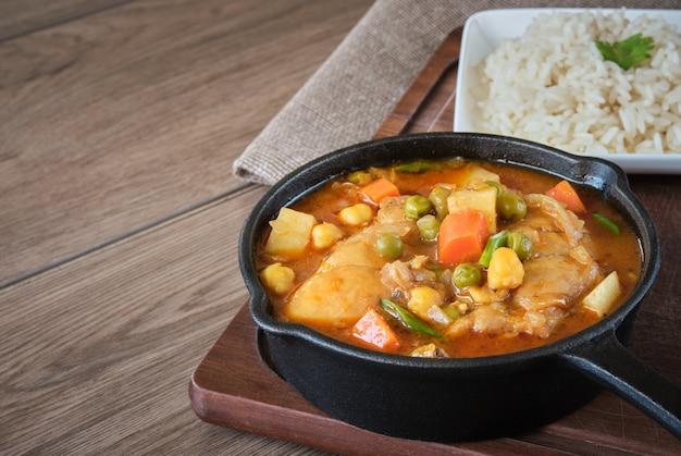 Pollo guisado con verduras papas, zanahorias, guisantes, garbanzos servidos con arroz
