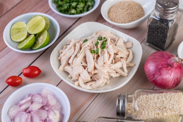 Pollo hervido cortado en trozos en un plato blanco sobre una mesa de madera.