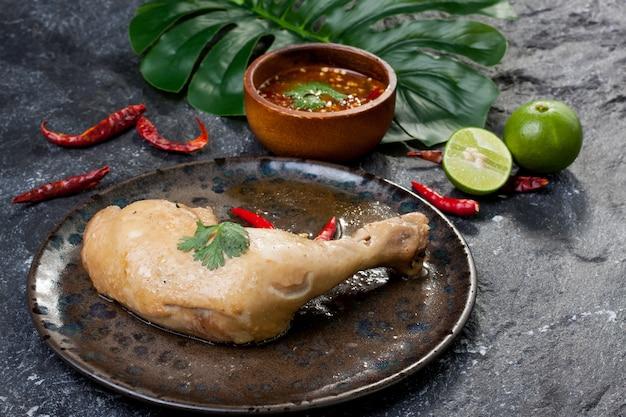 Pollo hervido con salsa de pescado en plato sobre roca negra.tailandia cocina asiática