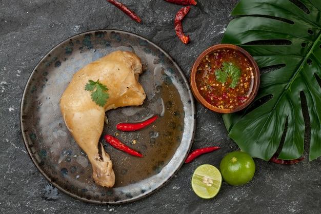 Pollo hervido con salsa de pescado en un plato en la vista superior de la roca negra.