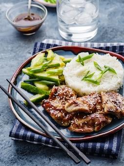 Pollo hoisin. cocina tradicional asiática. pollo con salsa, arroz y pepinos en vinagre.