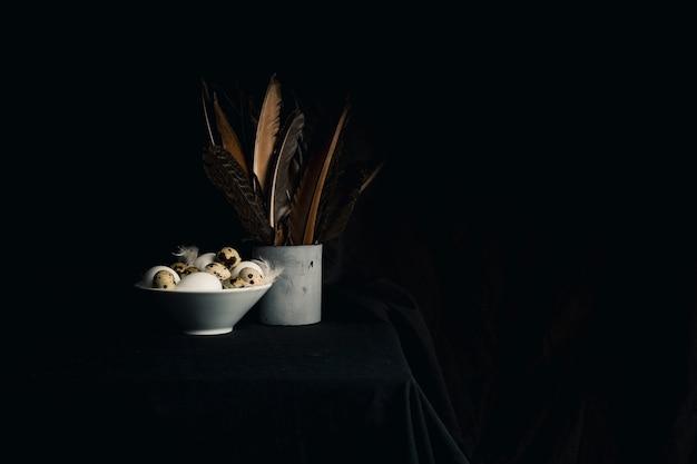 Pollo y huevos de codorniz entre plumas en un tazón cerca de las plumas en lata vieja