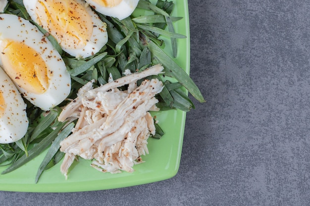 Pollo con huevos duros en placa verde.