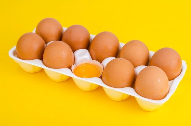 Pollo huevos marrones y yema de huevo en forma blanca.