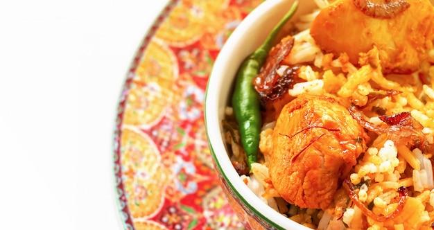 El pollo indio biryani sirvió con el fondo del blanco del raita del tomate del yogur. enfoque selectivo