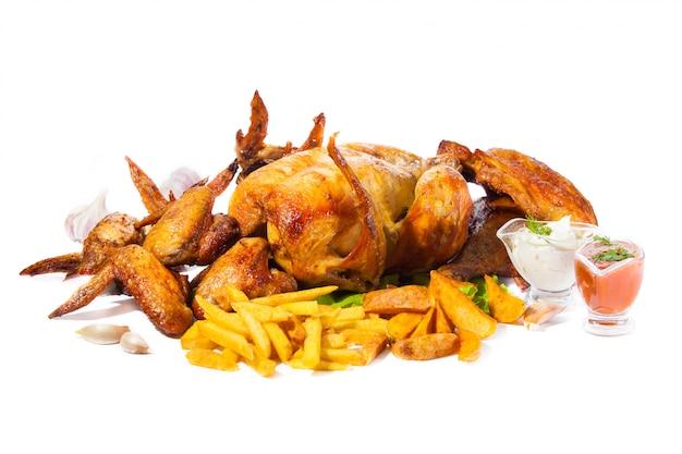 Pollo a la parrilla, alitas y muslos a la parrilla con papas fritas sobre fondo blanco aislado