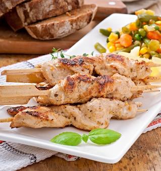 Pollo a la parrilla en brochetas de bambú