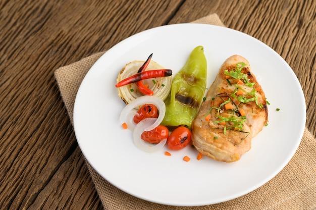 Pollo a la parrilla en un plato blanco con tomate, ensalada, cebolla, chile y salsa.