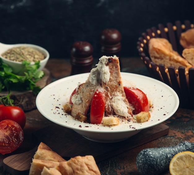 Pollo a la parrilla con queso mozarella y tomates.