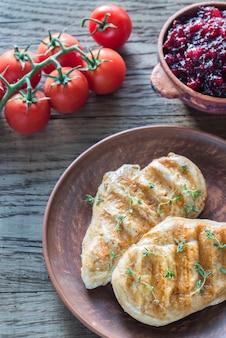 Pollo a la parrilla con salsa de arándanos y tomates cherry frescos