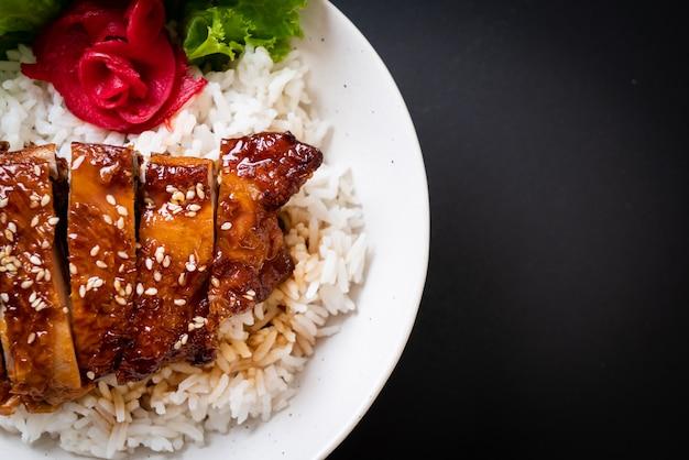 Pollo a la parrilla con salsa teriyaki sobre arroz cubierto