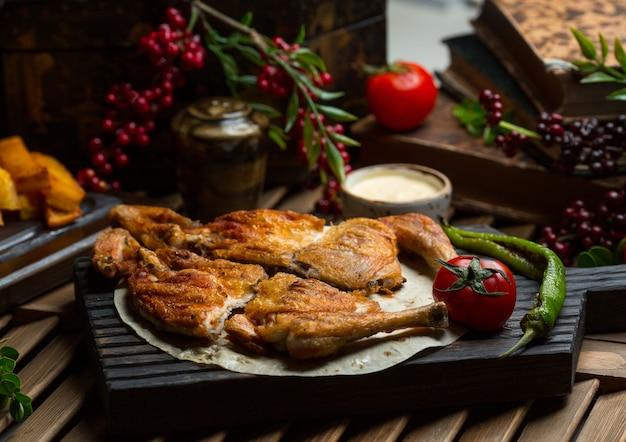 Pollo a la parrilla servido en lavash con pimiento asado y tomates