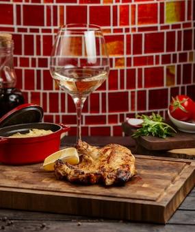 Pollo a la parrilla servido con limón y puré de papa en tablero de madera