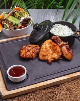 Pollo a la parrilla sobre tabla de madera con ensalada de verduras de eneldo de arroz salsa roja vista lateral