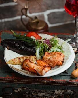 Pollo a la parrilla con tomate, berenjenas y hierbas.