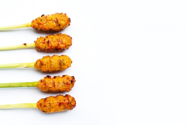 Pollo picado a la parrilla con pasta de curry y crema de coco en brochetas de hierba de limón. copia espacio