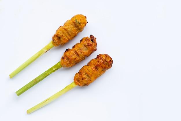 Pollo picado a la parrilla con pasta de curry y crema de coco en brochetas de hierba de limón.