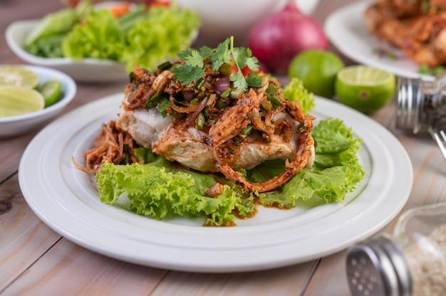 Pollo picado picante en un plato blanco completo con pepino, lechuga y guarniciones.