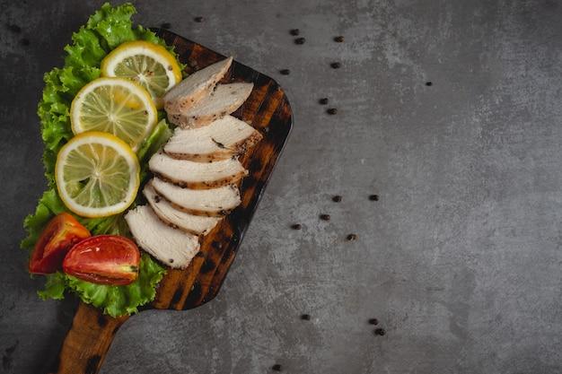 Pollo a la plancha sobre una tabla de cortar.