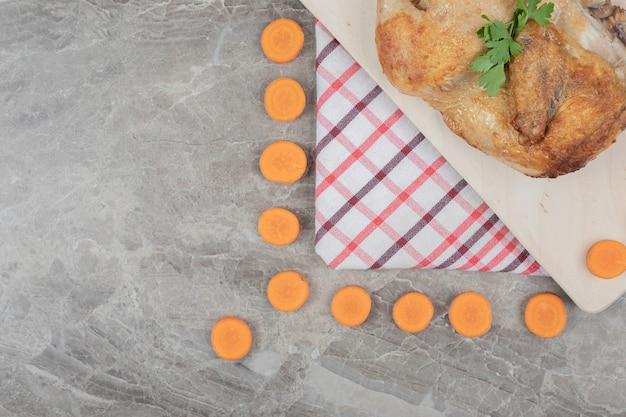 Pollo a la plancha sobre tabla de madera con rodajas de zanahoria. foto de alta calidad