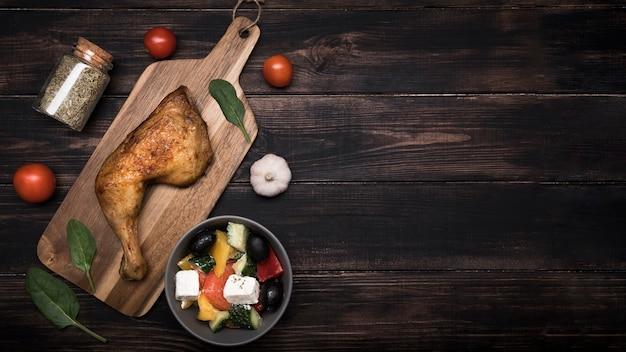 Pollo plano en tablero de madera e ingredientes con espacio de copia