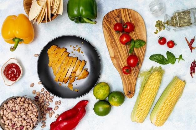 Pollo en plato y vegetales coloridos