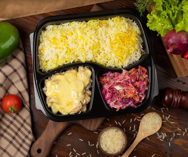 Pollo en salsa de queso fundido en crema con guarnición de arroz y ensalada de zanahoria con col