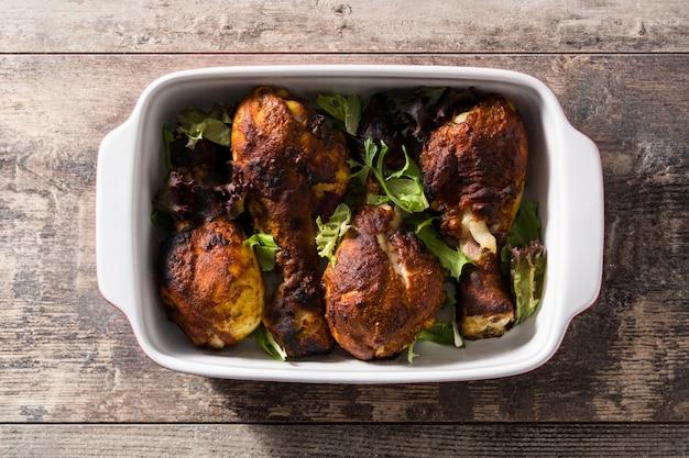 Pollo tandoori asado con arroz basmati en la mesa de madera. vista superior.