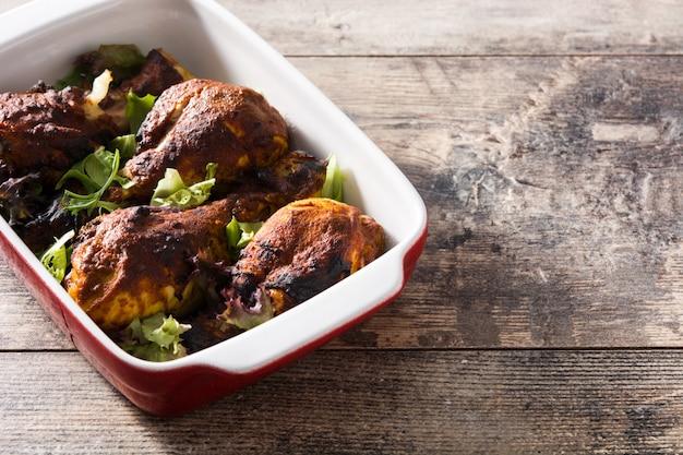 Pollo tandoori asado con arroz basmati en la mesa de madera.
