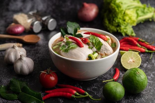 Pollo tom yum con chile, cilantro, chile seco, hojas de lima kaffir, champiñones y hierba de limón en un bol