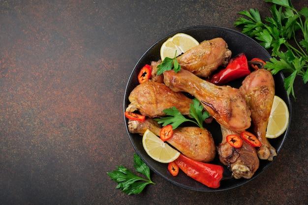 Pollos fritos con patas puntiagudas en una sartén de hierro fundido sobre una superficie oscura de hormigón o piedra. enfoque selectivo.