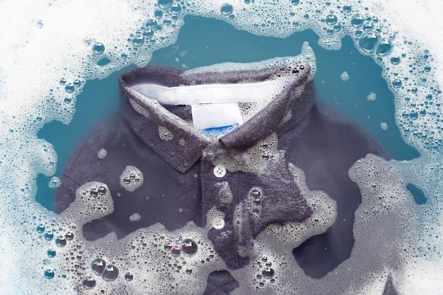 Polo gris remojo en detergente en polvo en disolución de agua. concepto de lavandería