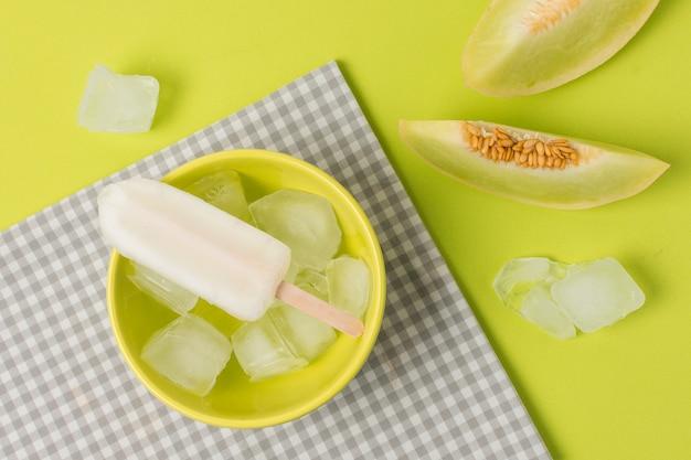 Polo de hielo en un tazón cerca de la servilleta y frutas frescas