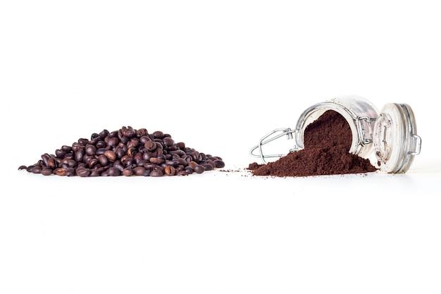 Polvo de café y granos de café aislados en blanco