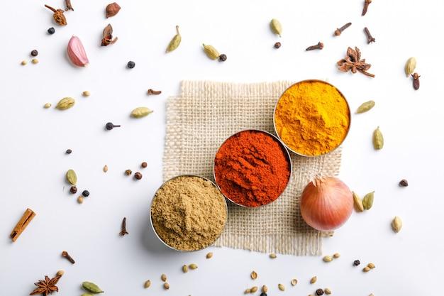Polvo de chiles rojo, especias de colores indios, polvo de cúrcuma, polvo de cilantro en mesa blanca
