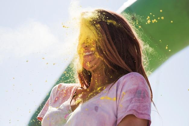 Polvo de color holi amarillo explota en la cara de la mujer.