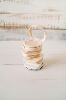 Un polvo compacto abierto sobre el apilado de esponja en mesa de madera