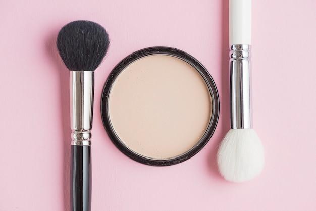 Polvo compacto y pinceles sobre fondo rosa