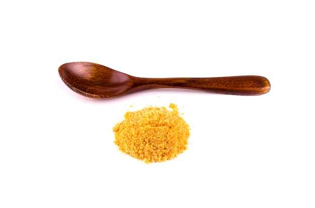 Polvo de curry y cuchara sobre el fondo blanco.