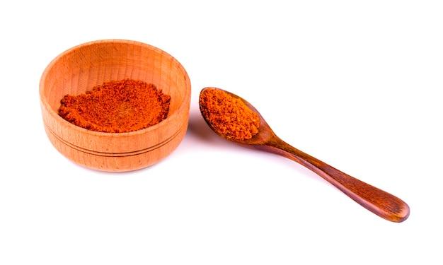 Polvo de curry en un recipiente sobre el fondo blanco.