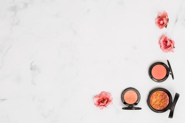 Polvo facial compacto con rosa rosa sobre fondo de mármol con textura